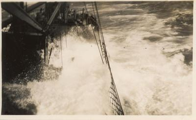 Photograph: Ship at sea with wave crashing onto starboard deck