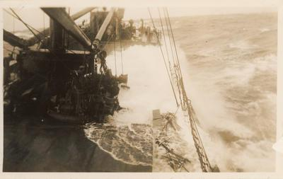Photograph: Ship at sea with wave crashing on starboard deck