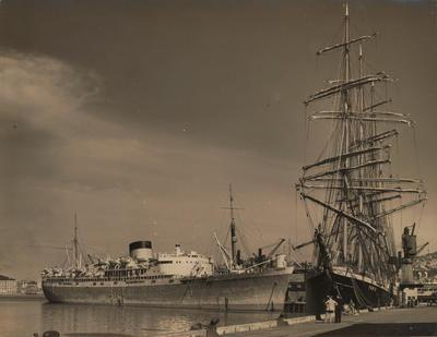Photograph: Barque PAMIR (1905) berthed at wharf with a passenger liner moored to starboard