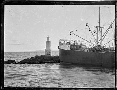 Glass plate: Steel hulled cargo vessel anchored near coastal beacon