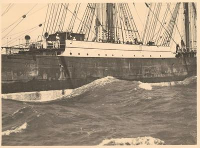 Photograph: PAMIR (1905), starborad side of hull while at sea, sailors on deck visible